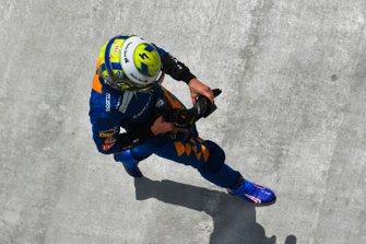 Lando Norris, McLaren, walks back to the garage after a failure ends his race