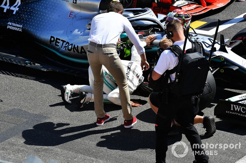 Lewis Hamilton, Mercedes AMG F1, looks under his car as Paul di Resta, Sky Sports F1, interviews him after Qualifying