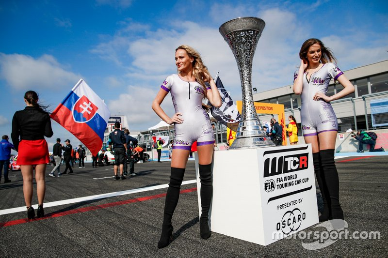 The trophy and girls on the starting grid