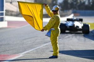 A marshal holds a yellow flag