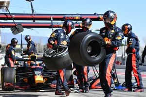 Wheels are carried by mechanics during a pit stop