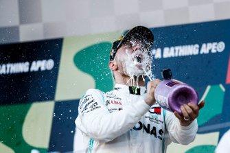 Valtteri Bottas, Mercedes AMG F1, primo classificato, beve Champagne sul podio