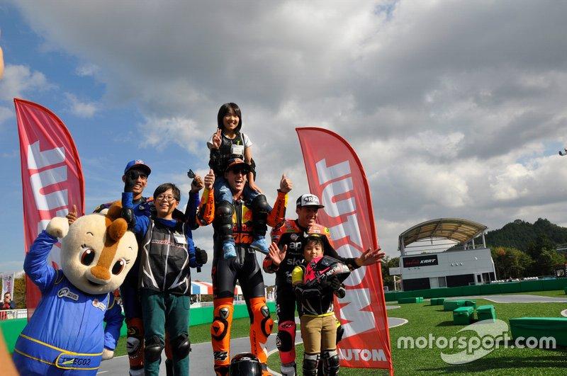 Los Espargaró (Pol y Aleix) celebran junto a Oliveira el podio de la minicarrera