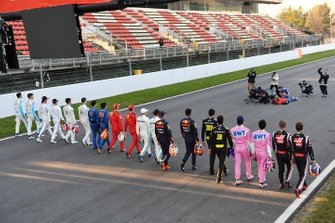 The drivers walk along the track toward a group of photographers
