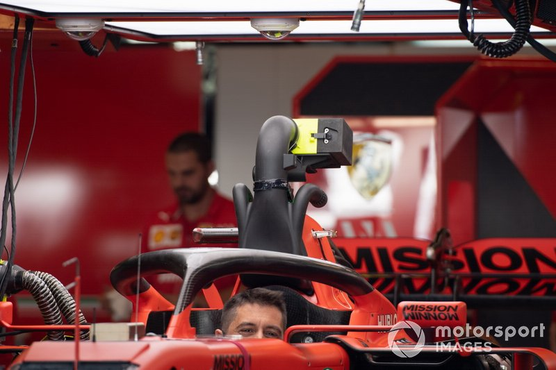 A Ferrari mechanic sits in the cockpit of a Ferrari SF90