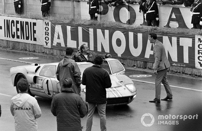Denis Hulme cabalga en la puerta abierta de su Shelby American Inc, Ford GT-40 Mk II después de la carrera