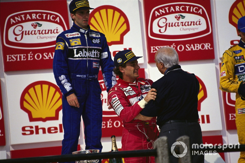 Ayrton Senna, McLaren embraces Juan Manuel Fangio on the podium, with Damon Hill, Williams