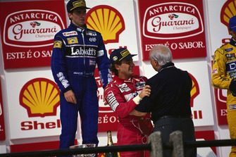 Ayrton Senna, McLaren embraces Juan Manuel Fangio on the podium, with Damon Hill, Williams