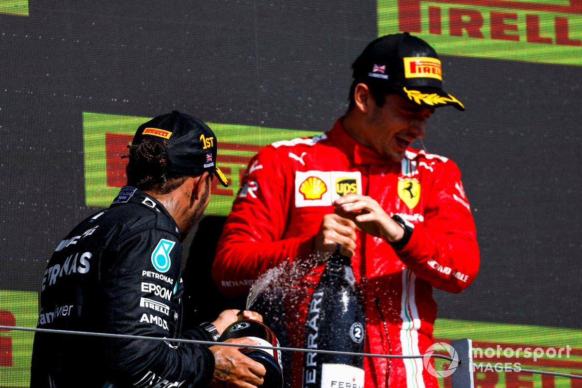Lewis Hamilton, Mercedes, primo classificato, e Charles Leclerc, Ferrari, secondo classificato, spruzza Champagne sul podio