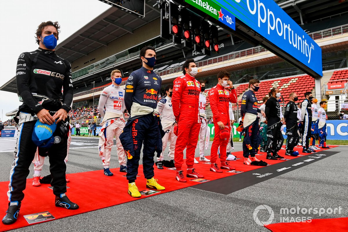 Los pilotos se ponen en pie para escuchar el himno nacional antes de la salida