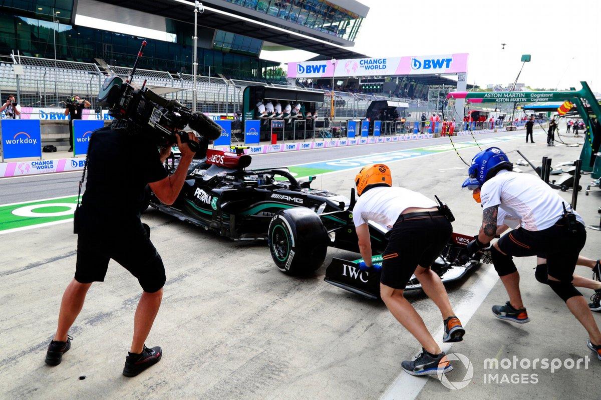 Miembros del equipo de pits de McLaren intentan asistir a Valtteri Bottas, Mercedes W12, después de que hizo un trompo en el pit lane