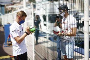Mick Schumacher, Haas F1, signs a miniature helmet for a fan