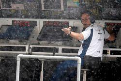 Un miembro del equipo Williams comprueba la caída de lluvia de la pared de boxes