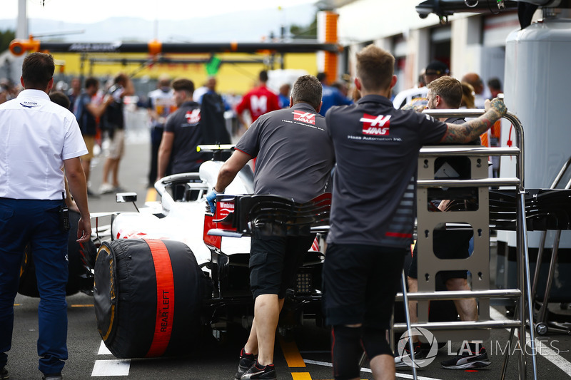 Haas team members guard a Haas F1 Team VF-18 in the pit lane