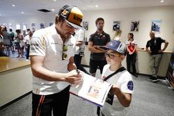 Fernando Alonso, McLaren, signs autographs for the grid kids