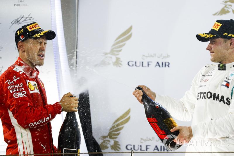 Sebastian Vettel, Ferrari, 1st position, and Valtteri Bottas, Mercedes AMG F1, 2nd position, spray Waard, a non-alcoholic Champagne Rose Water substitute, on the podium