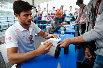 Carlos Sainz Jr., McLaren, signs autographs