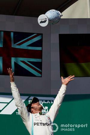 Il primo classificato Lewis Hamilton, Mercedes AMG F1, lancia il suo trofeo in aria per festeggiare