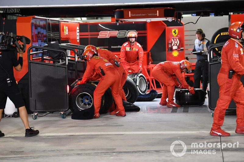 La pit crew Ferrari si prepara per sostituire l'ala anteriore di Sebastian Vettel