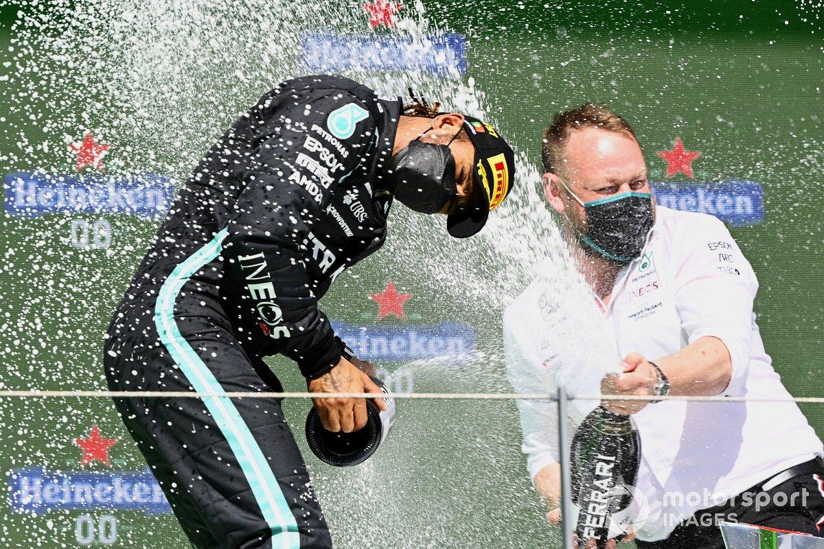 Lewis Hamilton, Mercedes, primo classificato, e il delegato per il trofeo Mercedes festeggiano con lo Champagne