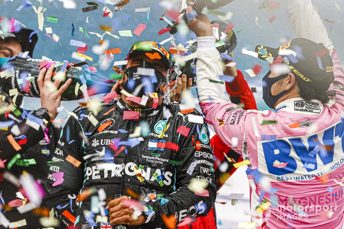 Sebastian Vettel, Ferrari, 3rd position, and Sergio Perez, Racing Point, 2nd position, pour Champagne down the back of Lewis Hamilton, Mercedes-AMG F1, 1st position, on the podium