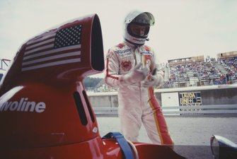 Mario Andretti stands next to his Parnelli VPJ4B Ford in the pits