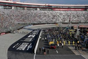 Drivers, crew and fans stand for the national anthem