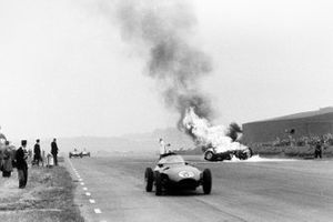 Tony Brooks's BRM P25 burns after he had crashed as the car of Harry Schell, Vanwall VW2 passes