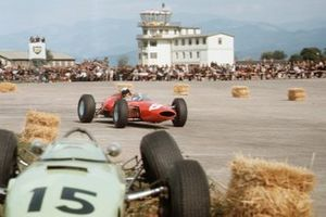 Lorenzo Bandini Ferrari 156 passes the crashed BRP 1-BRM of Trevor Taylor