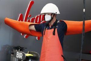 Un membro del Team Envision Virgin indossa dispositivi di protezione individuale nel garage