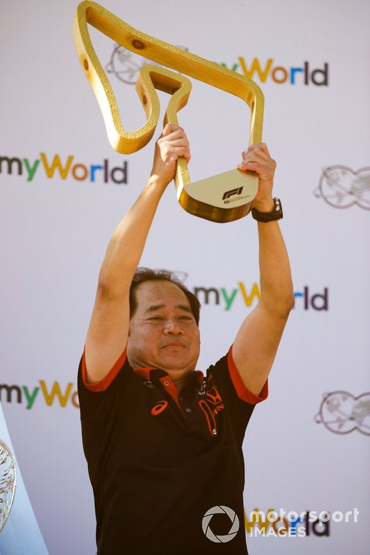 Masashi Yamamoto, General Manager, Honda Motorsport on the podium with the trophy