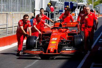 Ferrari mechanics push the car of Sebastian Vettel, Ferrari SF90 down the pit lane
