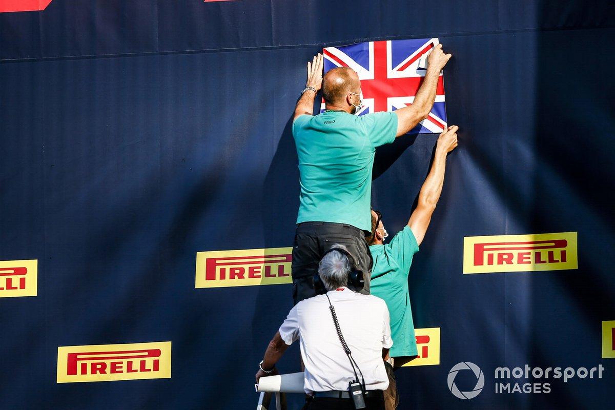 Организаторы закрепляют британский флаг над подиумом перед церемонией награждения
