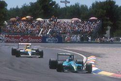 Ivan Capelli, Leyton House CG901 Judd prend la tête de la course pour la première fois, avec Riccardo Patrese, Williams FW13B Renault deuxième derrière lui.