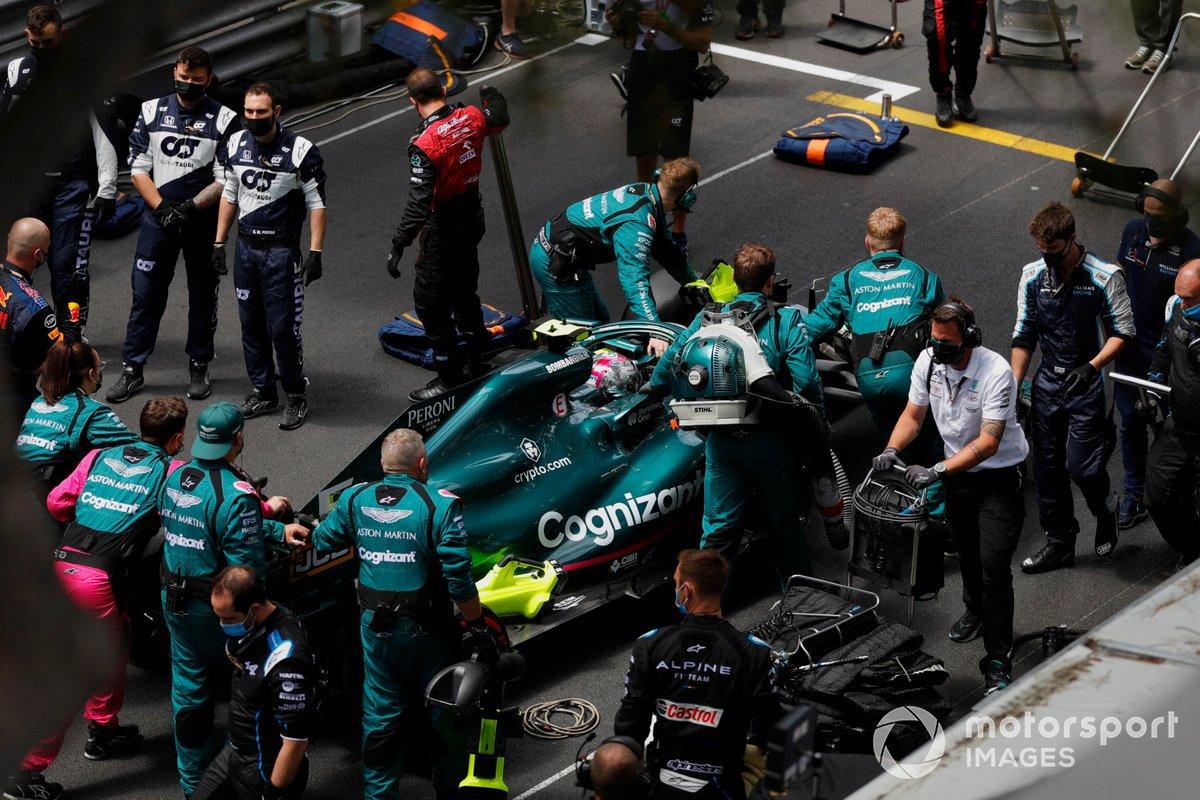 Mecánicos empujan el coche de Sebastian Vettel, Aston Martin AMR21
