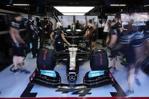 The Lewis Hamilton Mercedes W12 is worked on in the pit garage