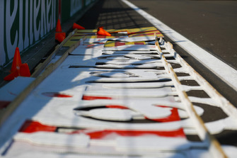 Stencils used for trackside branding and sponsorship rest on the circuit