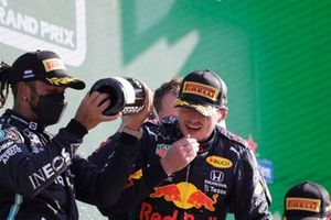 Lewis Hamilton, Mercedes, 2nd position, pours Champagne over Max Verstappen, Red Bull Racing, 1st position, on the podium