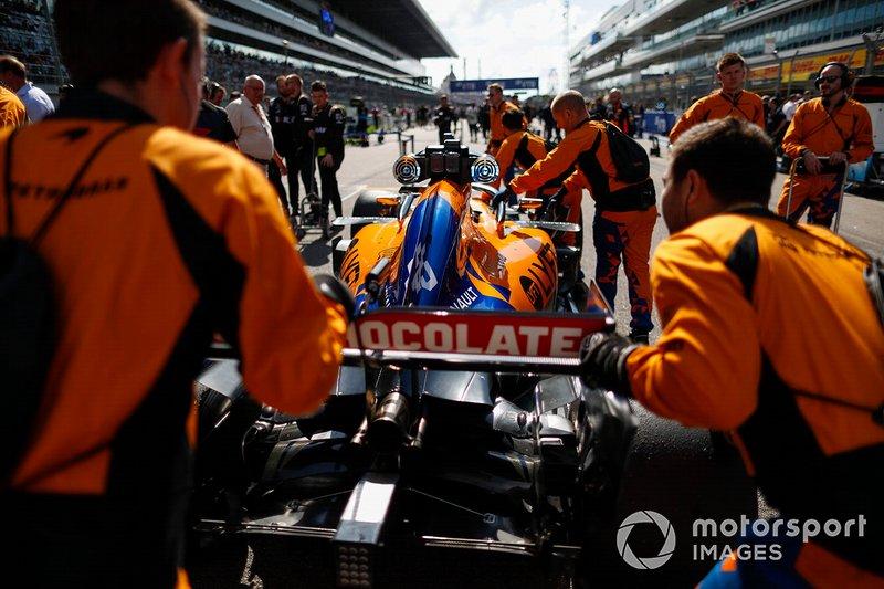 Carlos Sainz Jr, McLaren, llega a la parrilla con sus mecánicos