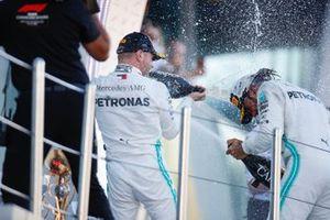 Winner Lewis Hamilton, Mercedes AMG F1, and Valtteri Bottas, Mercedes AMG F1, spray champagne on the podium
