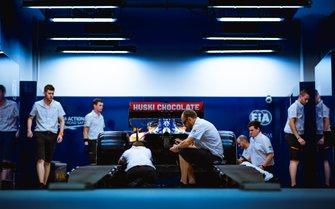 Los mecánicos de McLaren revisando el coche en la caja de la FIA