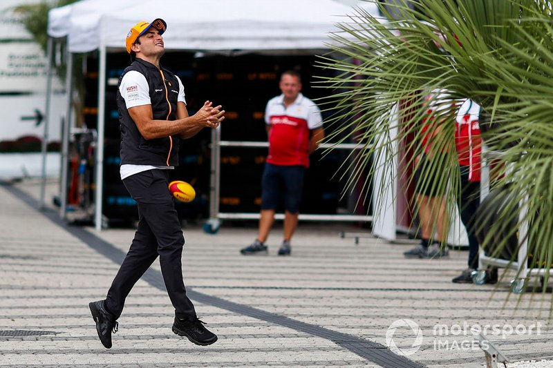 Carlos Sainz Jr., McLaren, drops a rugby ball