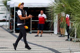 Carlos Sainz Jr., McLaren, drops a rugby ball