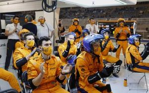 The McLaren pit crew applauds the efforts of their drivers in the garage