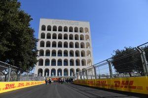Team members walk by the Palazzo della Civilta Italiana