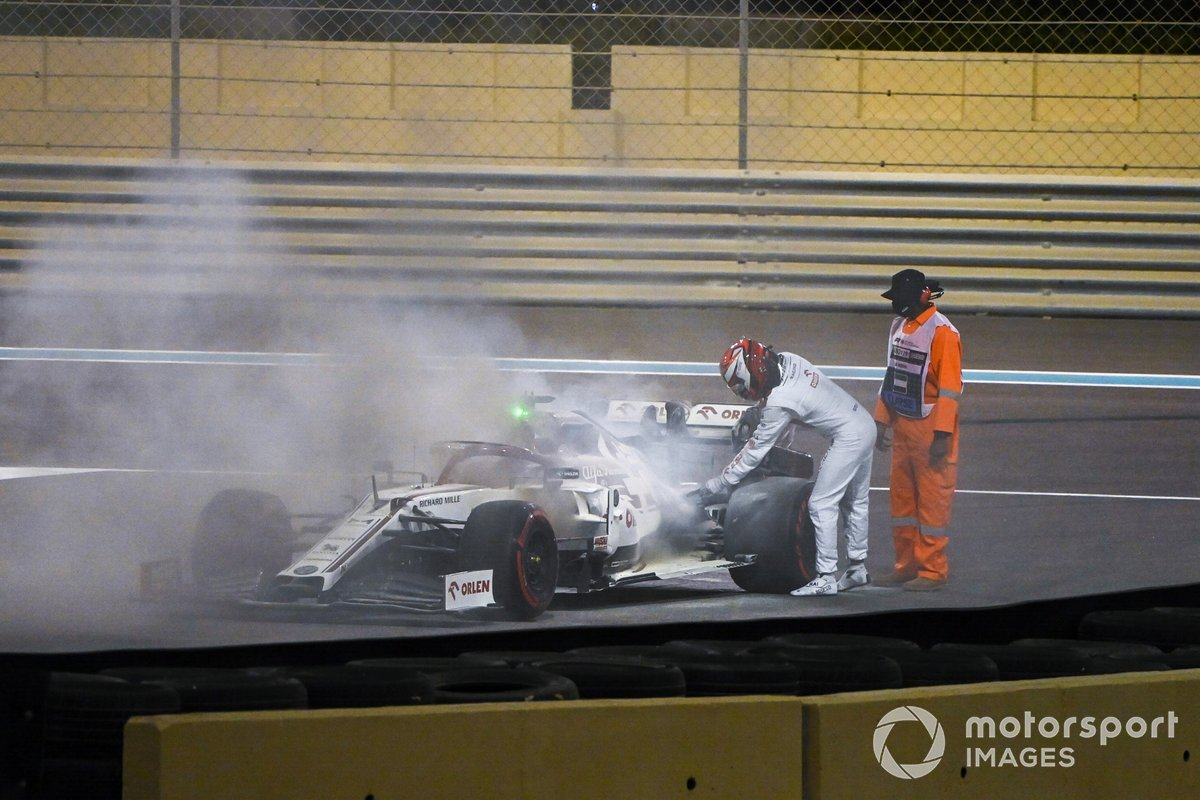 Kimi Raikkonen, Alfa Romeo Racing C39, assists a marshal in extinguishing a fire in his car