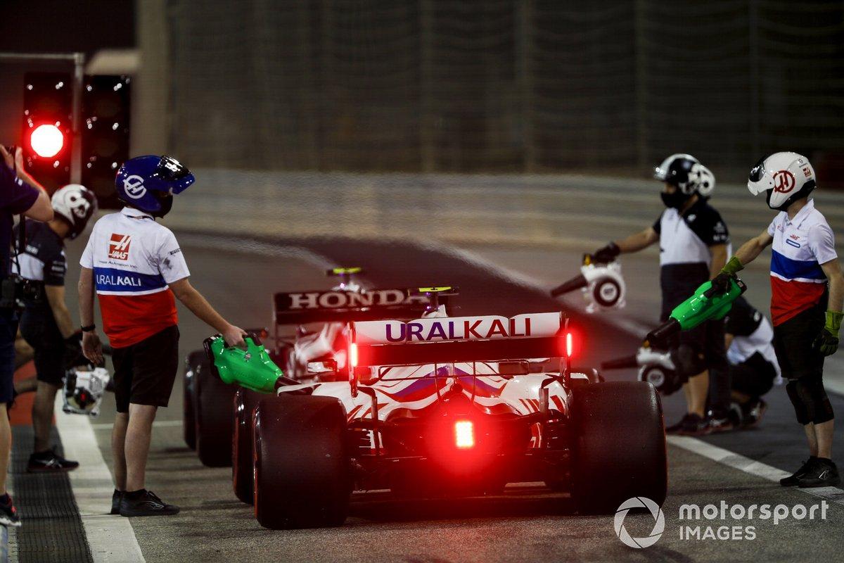 Des mécaniciens refroidissent la monoplace de Mick Schumacher, Haas VF-21 dans la voie des stands