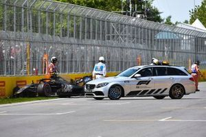 The Medical Car and marshals attend to the damaged car of Kevin Magnussen, Haas F1 Team VF-19