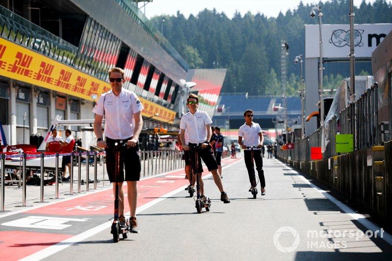 Lando Norris, McLaren y miembros de McLaren en patinetes