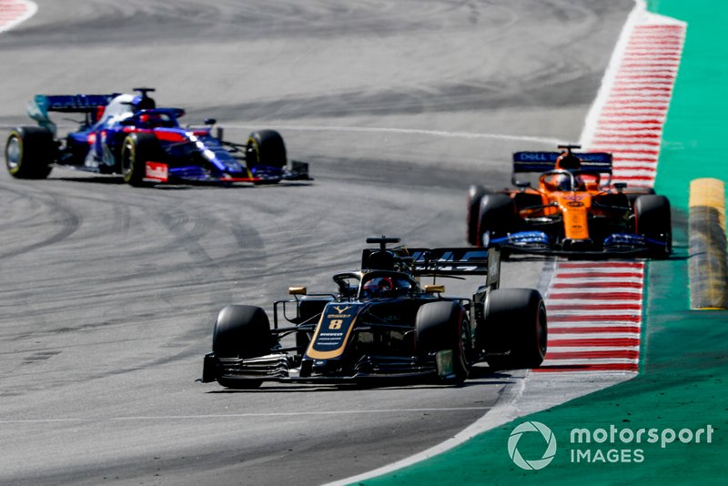 Romain Grosjean, Haas F1 Team VF-19, leads Carlos Sainz Jr., McLaren MCL34, and Daniil Kvyat, Toro Rosso STR14